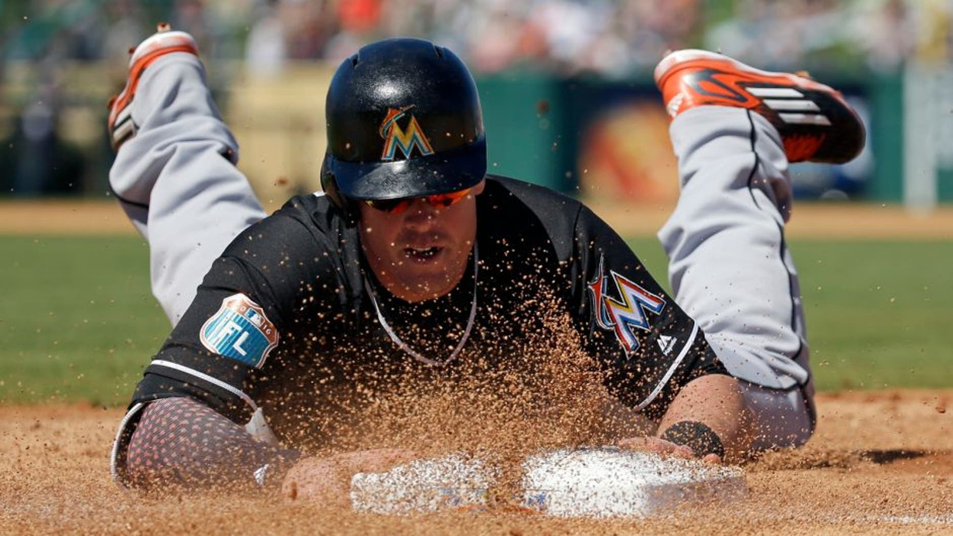 Miami Marlins' Justin Bour slides back to first base after an infield line drive was caught in the first inning of a spring training baseball game against the Detroit Tigers, Sunday, March 6, 2016, in Lakeland, Fla. (AP Photo/John Raoux)