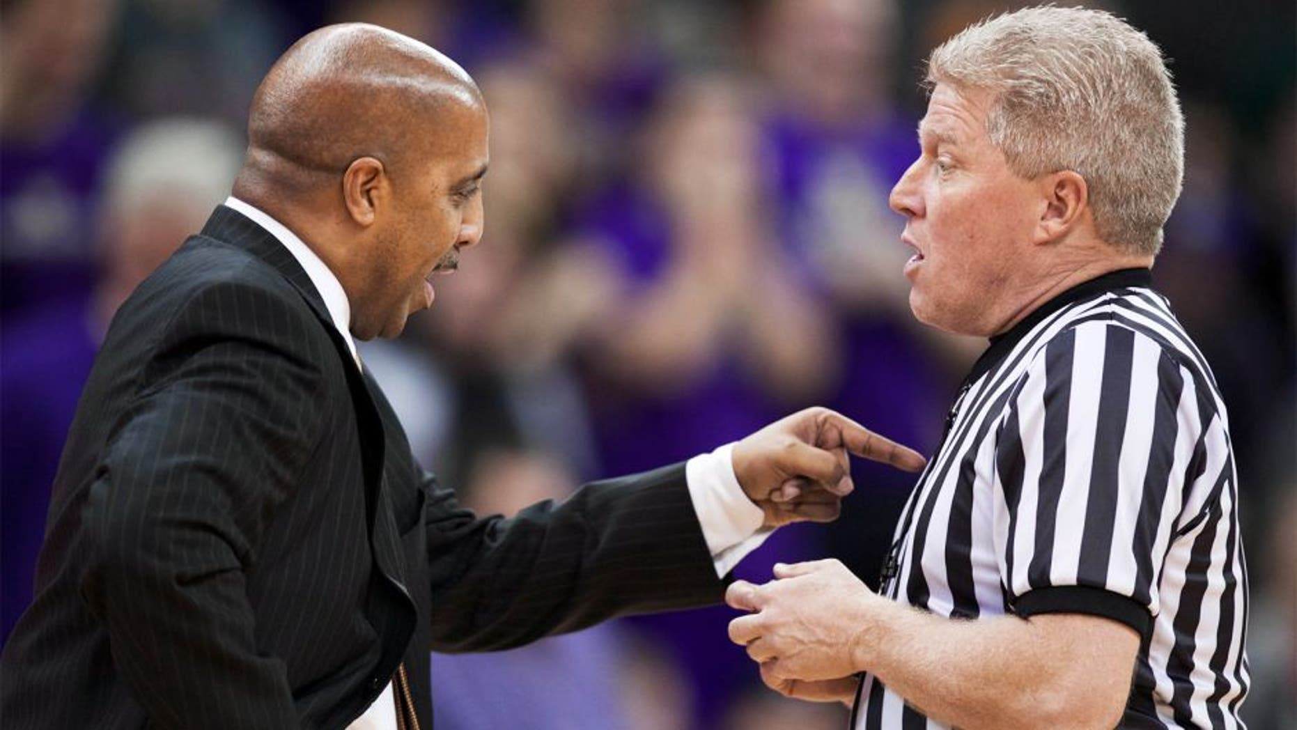 Washington head coach Lorenzo Romar, left, disputes a call with an official in the second half of an NCAA college basketball game against UCLA, Thursday March 6, 2014, in Seattle. UCLA won 91-82. (AP Photo/Stephen Brashear)