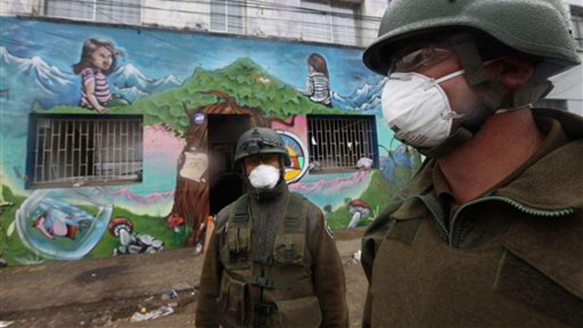 Soldiers wear masks as they patrol near a school in Talcahuano, Chile, Sunday, March 7, 2010.  An 8.8-magnitude earthquake struck central Chile on Feb. 27, causing widespread damage. (AP Photo/Silvia Izquierdo)