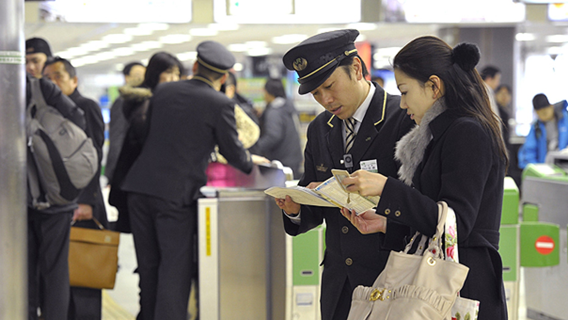 March 9: Japan Railway Sendai Station staff help stranded bullet train passengers as the high-speed train service is suspended at the station in Sendai, north of Tokyo, following a magnitude 7.3 earthquake hit northern Japan.