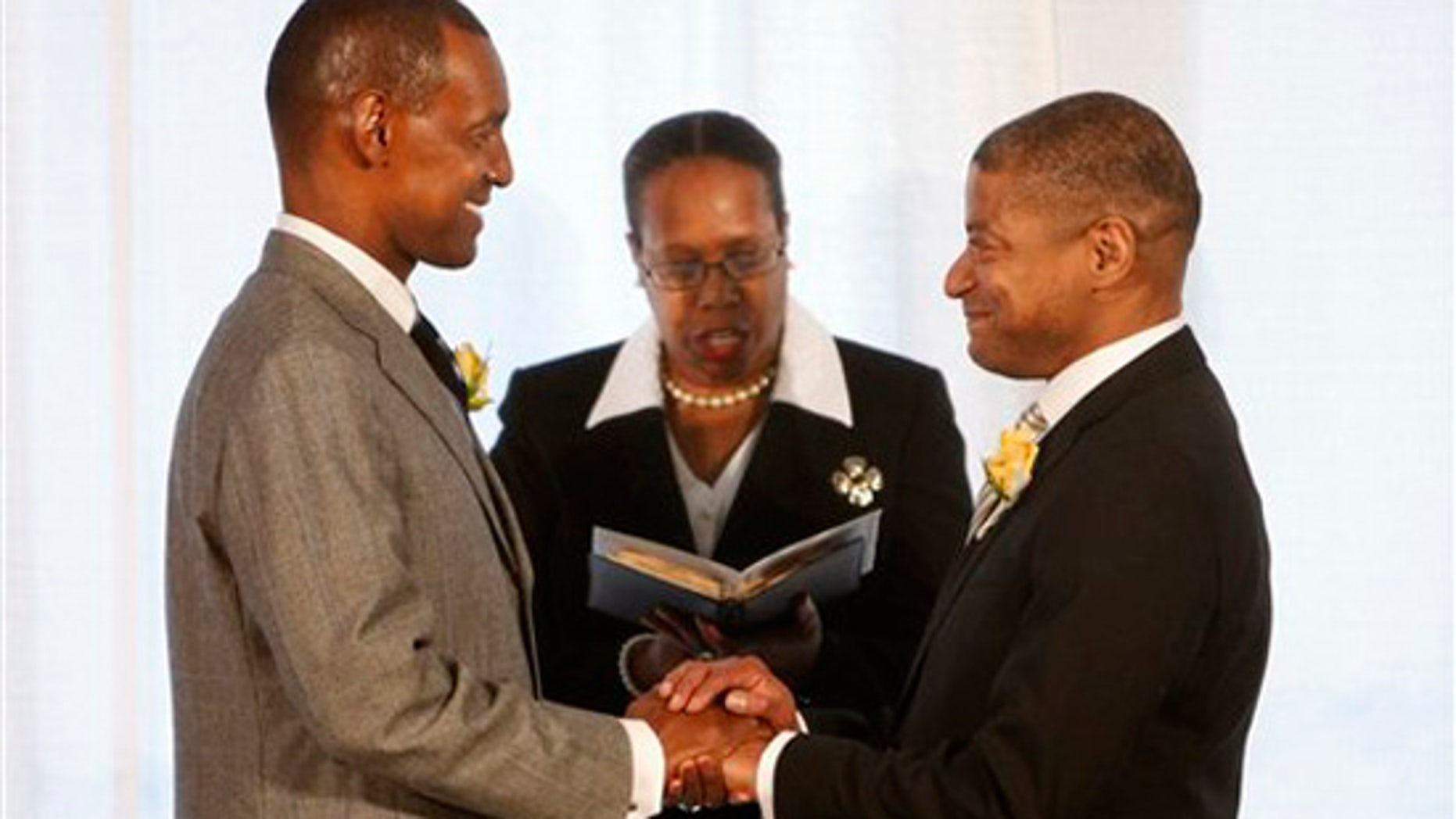 """Rocky Galloway, left, and Reginald Stanley are pronounced """"partners for life"""" by Rev. Sylvia E. Sumter during their marriage ceremony Tuesday, March 9, 2010, the first day that gay marriage is legal in Washington. (AP)"""