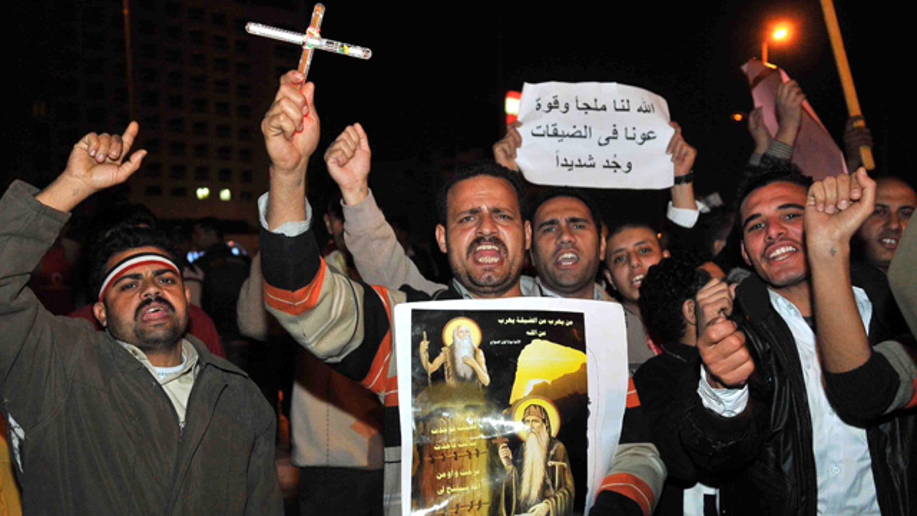 """March 8: Egyptian Copts carry a cross, a picture showing saints along a banner in Arabic that reads: """"God is our shelter and strength, he will help us in hard times"""" during a protest in downtown Cairo, Egypt."""