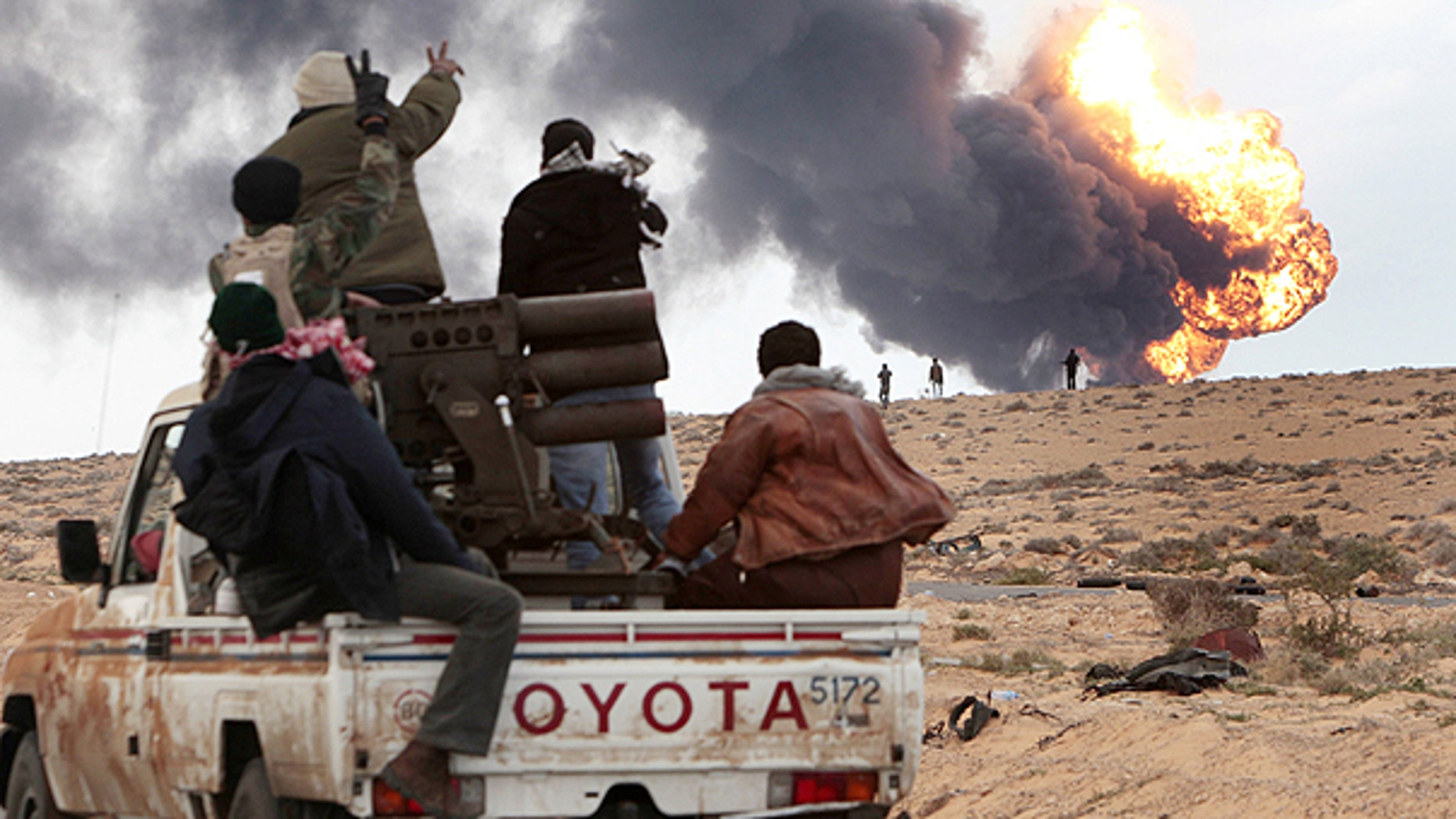 March 9: Anti-Qaddafi rebels ride on a truck with a multiple rocket launcher, as flames rises from a fuel storage facility that was attacked during fighting with pro-fighters, in Sedra, eastern Libya.
