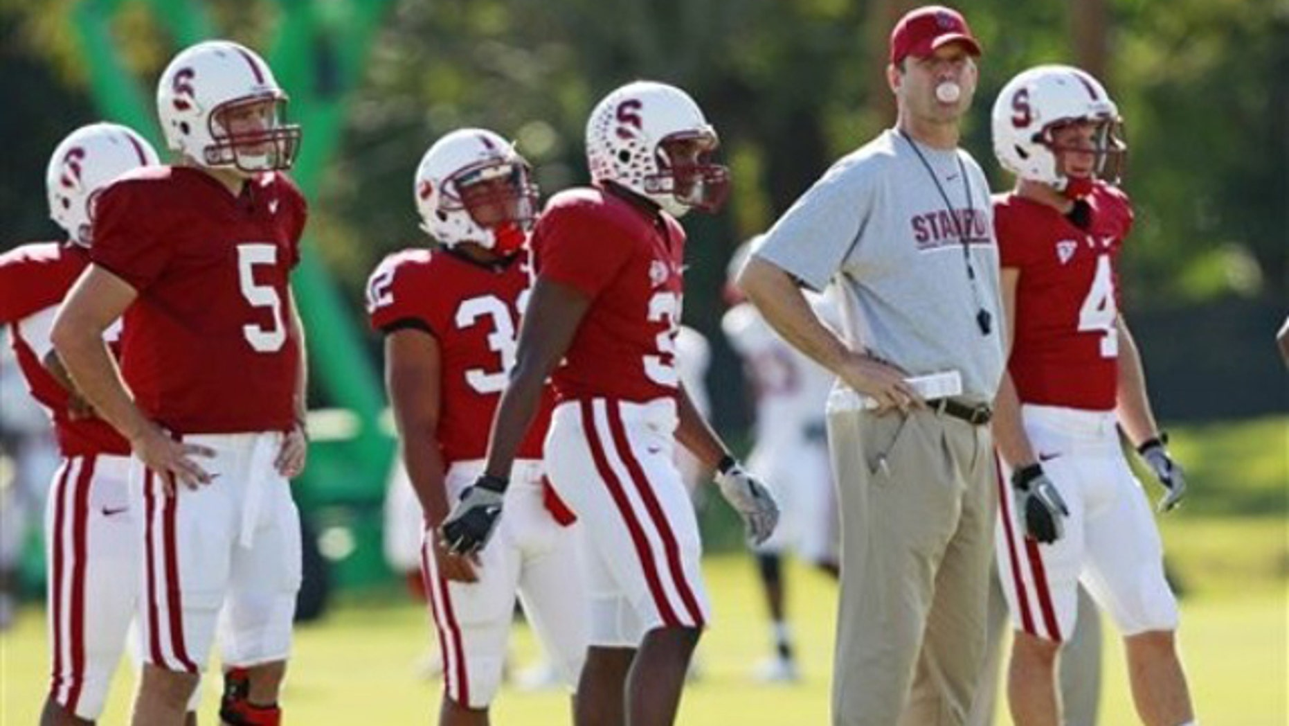 Stanford head coach Jim Harbaugh, second from right, blows a bubble as he watches his team practice at Barry University in Miami Shores, Fla., Wednesday, Dec. 29, 2010.