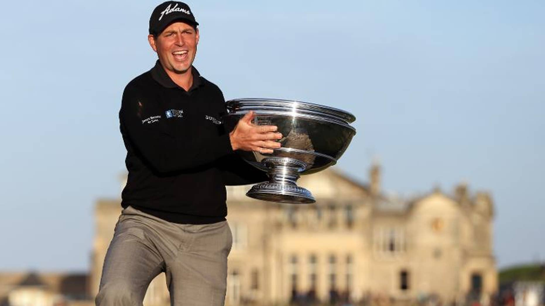 English golfer David Howell poses on the Swilcan Bridge with the trophy after winning the The Alfred Dunhill Links Championships golf competition on The Old Course at St Andrews, Fife, Scotland on September 29, 2013.