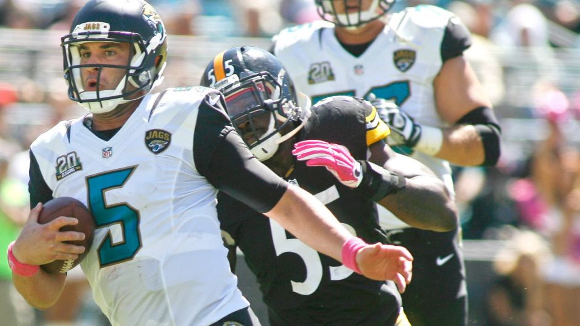 Oct 5, 2014; Jacksonville, FL, USA; Jacksonville Jaguars quarterback Blake Bortles (5) runs past Pittsburgh Steelers outside linebacker Arthur Moats (55) for a first down in the first quarter of their game at EverBank Field. Mandatory Credit: Phil Sears-USA TODAY Sports