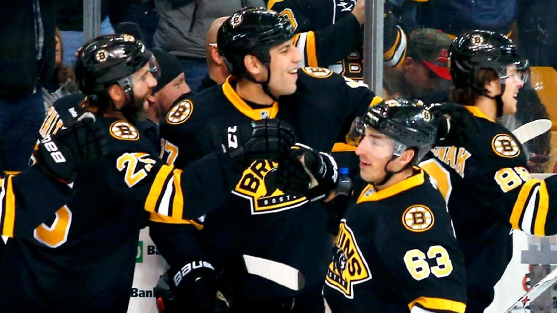Mar 8, 2015; Boston, MA, USA; Boston Bruins left wing Brad Marchand (63) is congratulated at the bench by Boston Bruins center Maxime Talbot (25) and left wing Milan Lucic (17) after scoring against the Detroit Red Wings during the first period at TD Garden. Mandatory Credit: Winslow Townson-USA TODAY Sports