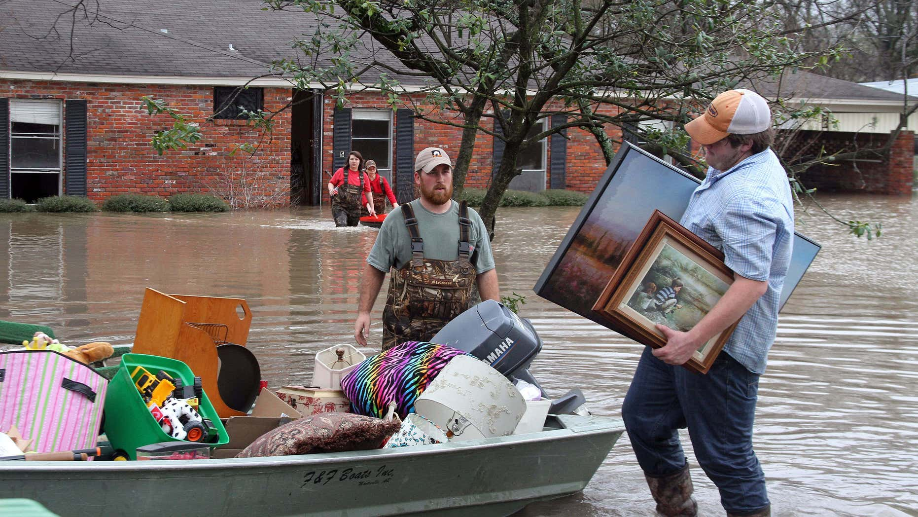 Volunteers return to a flooded house in Clarksdale, Miss., Friday, March 11, 2016, to assist the owners retrieve personal items as flood waters continued to rise following another morning of rain.