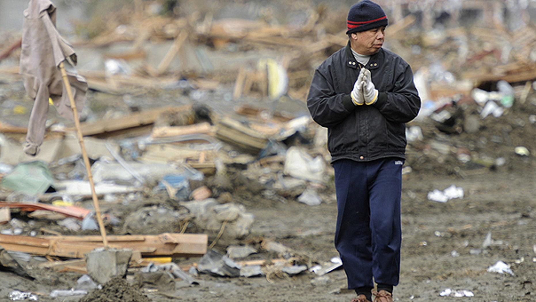 March 15: A man prays his family members at tsunami-devastated area in Rikuzentakata, Iwate prefecture, Japan.