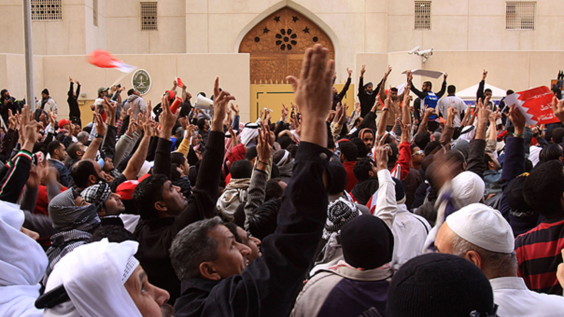 March 15: Anti-government protesters gesture in front of the Saudi embassy in Manama, Bahrain.