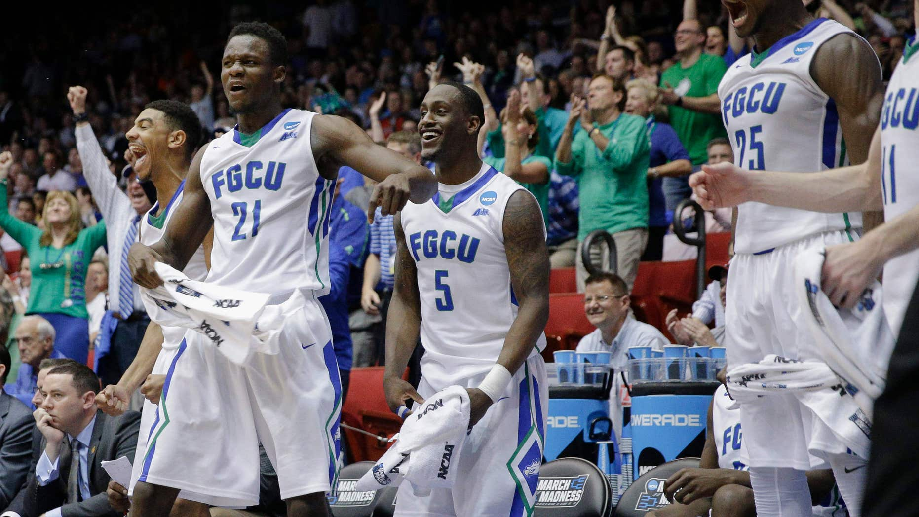 Florida Gulf Coast's Demetris Morant (21), Zach Johnson (5), and Marc Eddy Norelia (25) react after Brian Greene Jr., not pictured, dunks in the second half of a First Four game of the NCAA college basketball tournament against Fairleigh Dickinson, Tuesday, March 15, 2016, in Dayton, Ohio.