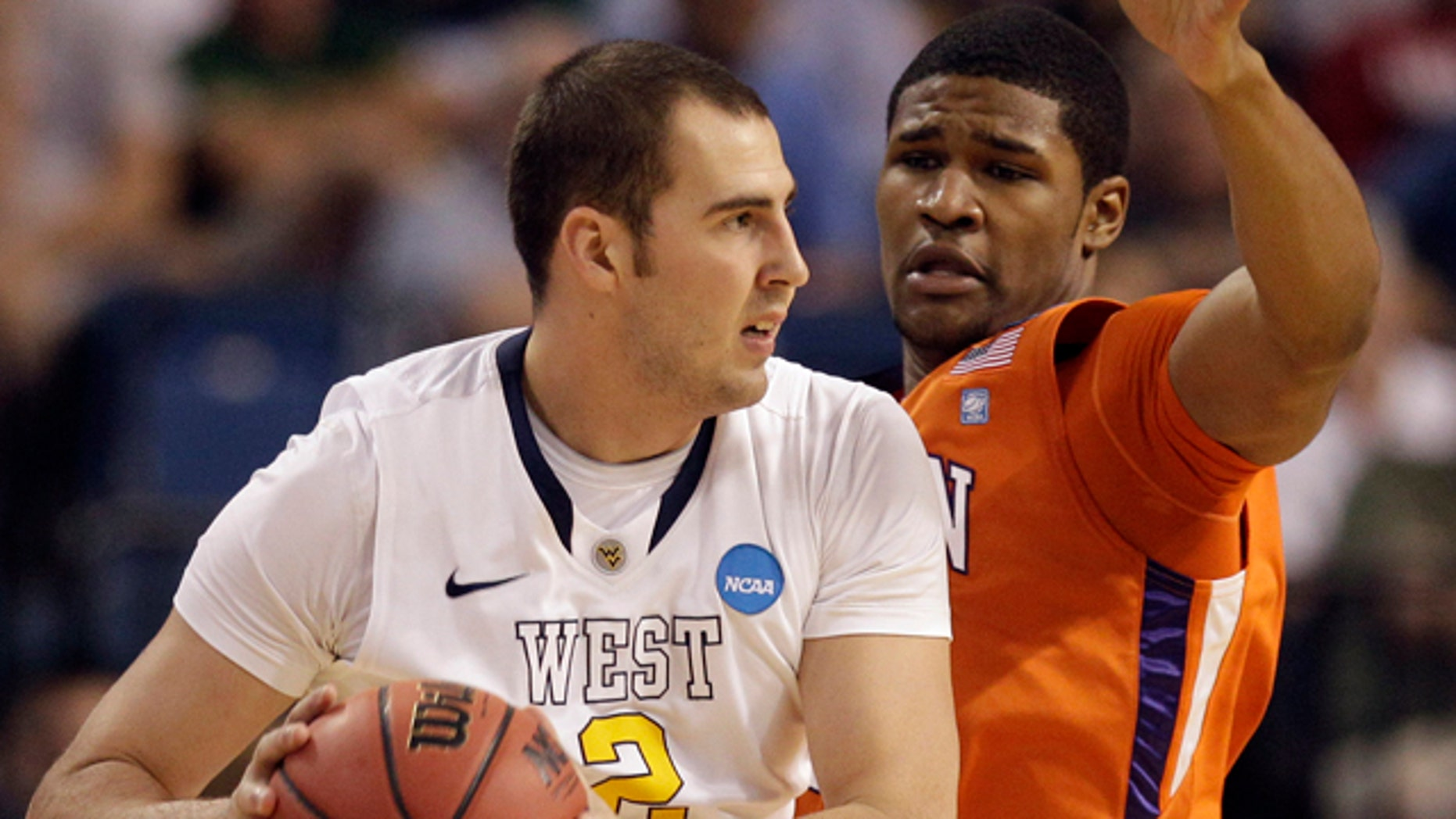 March 17: Clemson's Devin Booker (31) defends as West Virginia's Cam Thoroughman (2) attempts to pass during an East regional second round NCAA  tournament college basketball game in Tampa, Fla.