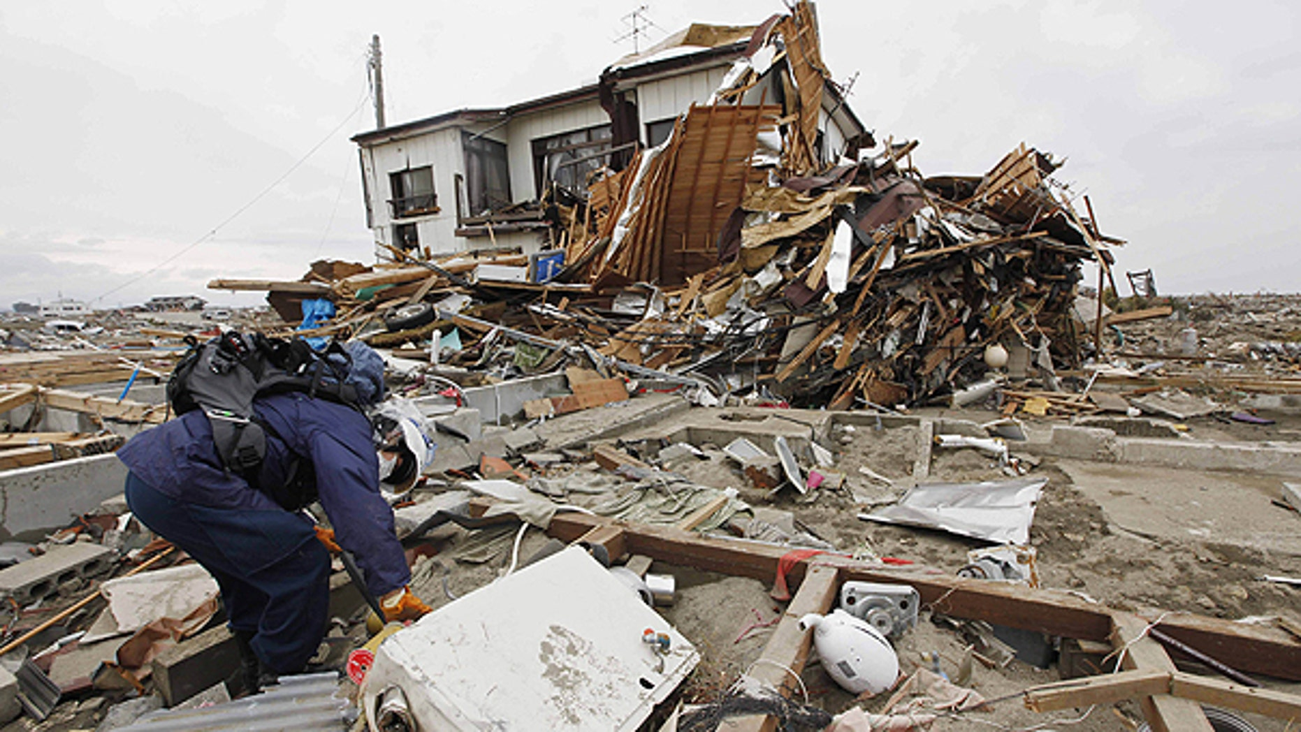 March 21: A rescue worker sifts through debris during a search in Natori, Miyagi Prefecture following the March 11 earthquake and tsunami that devastated the northeast coast of Japan.