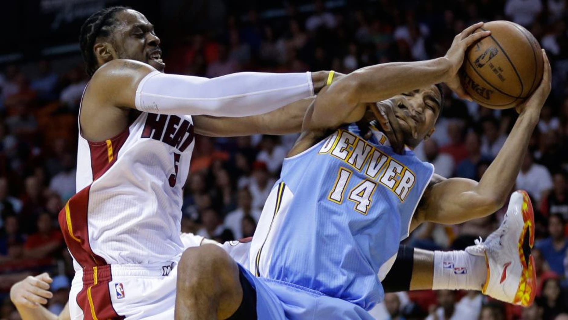 Miami Heat's Henry Walker, left, forces a jump ball as he defends Denver Nuggets' Gary Harris (14) during the second half of an NBA basketball game, Friday, March 20, 2015, in Miami. The Heat defeated the Nuggets 108-91. (AP Photo/Lynne Sladky)