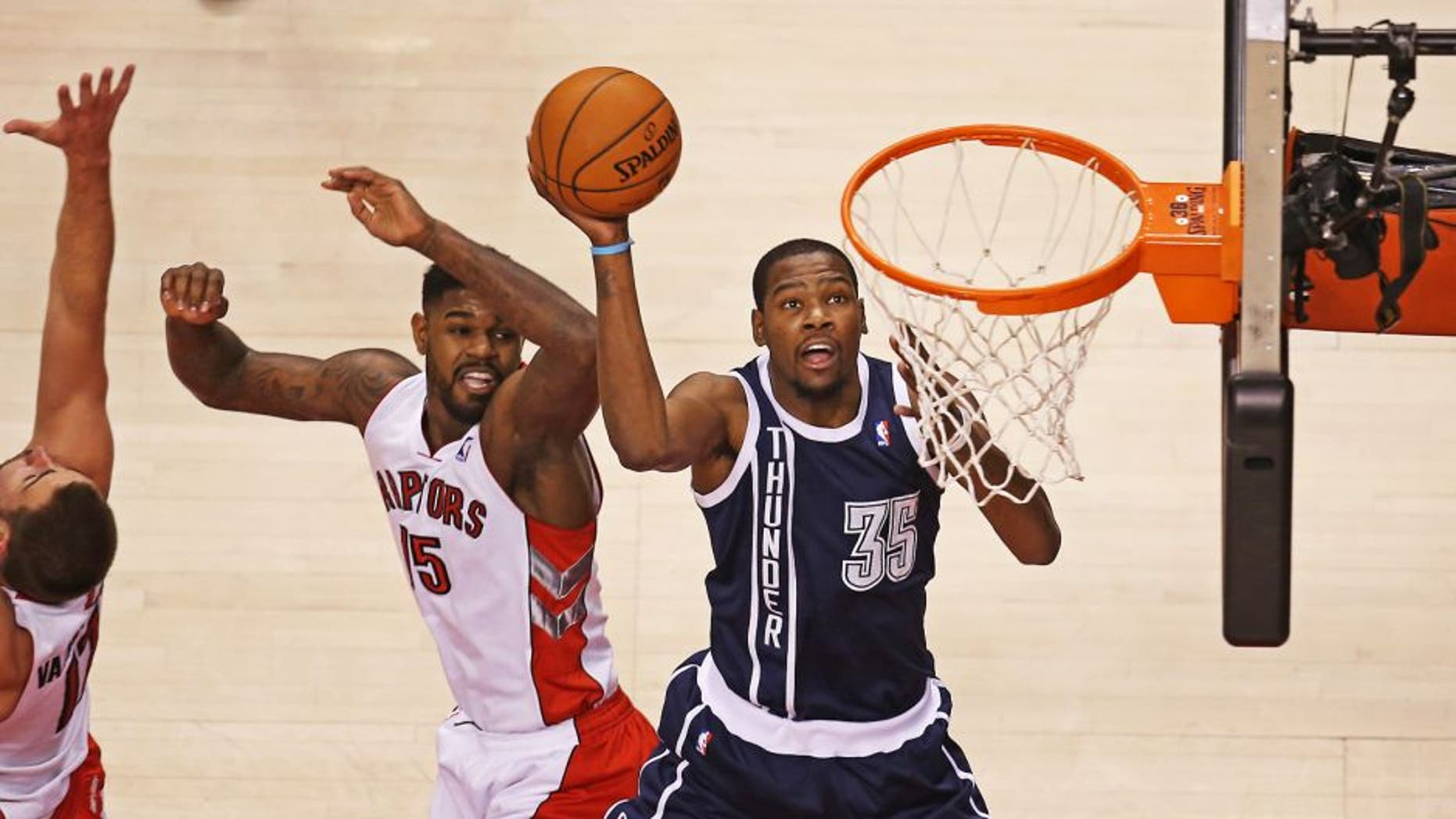 Mar 21, 2014; Toronto, Ontario, CAN; Oklahoma City Thunder forward Kevin Durant (35) goes to the basket and scores past Toronto Raptors forward Amir Johnson (15) at Air Canada Centre. Mandatory Credit: Tom Szczerbowski-USA TODAY Sports