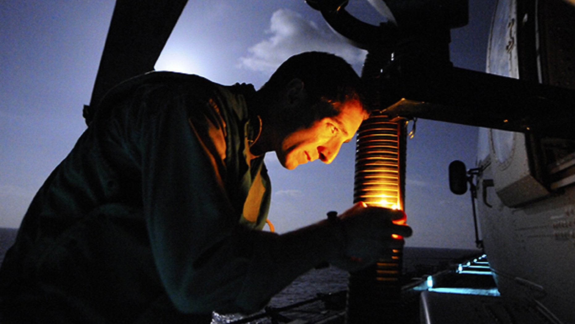 March 19: In this photo provided by the U.S. Navy, Naval Air Crewman 2nd Class Jordan Orr, assigned to Helicopter Sea Combat Squadron 22, checks the mount for a GAL-21 machine gun on a Sea Hawk helicopter on the flight deck of amphibious assault ship USS Kearsarge in preparation for operations against Libya in the Mediterranean Sea.