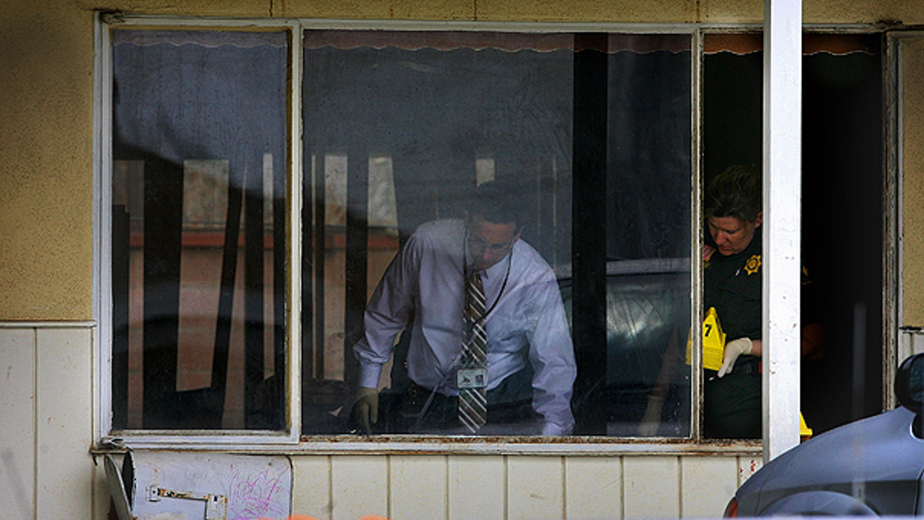 March 23: San Bernardino Sheriff's investigators and other personnel gather evidence at the scene where there were multiple stabbings in San Bernardino, Calif.
