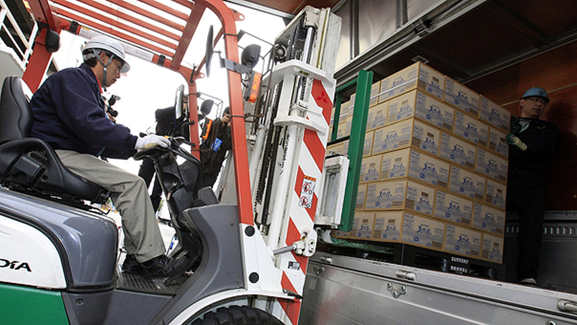 March 24: A worker loads boxes containing bottles of water onto a truck to distribute to households with infants, at a warehouse in Tokyo.