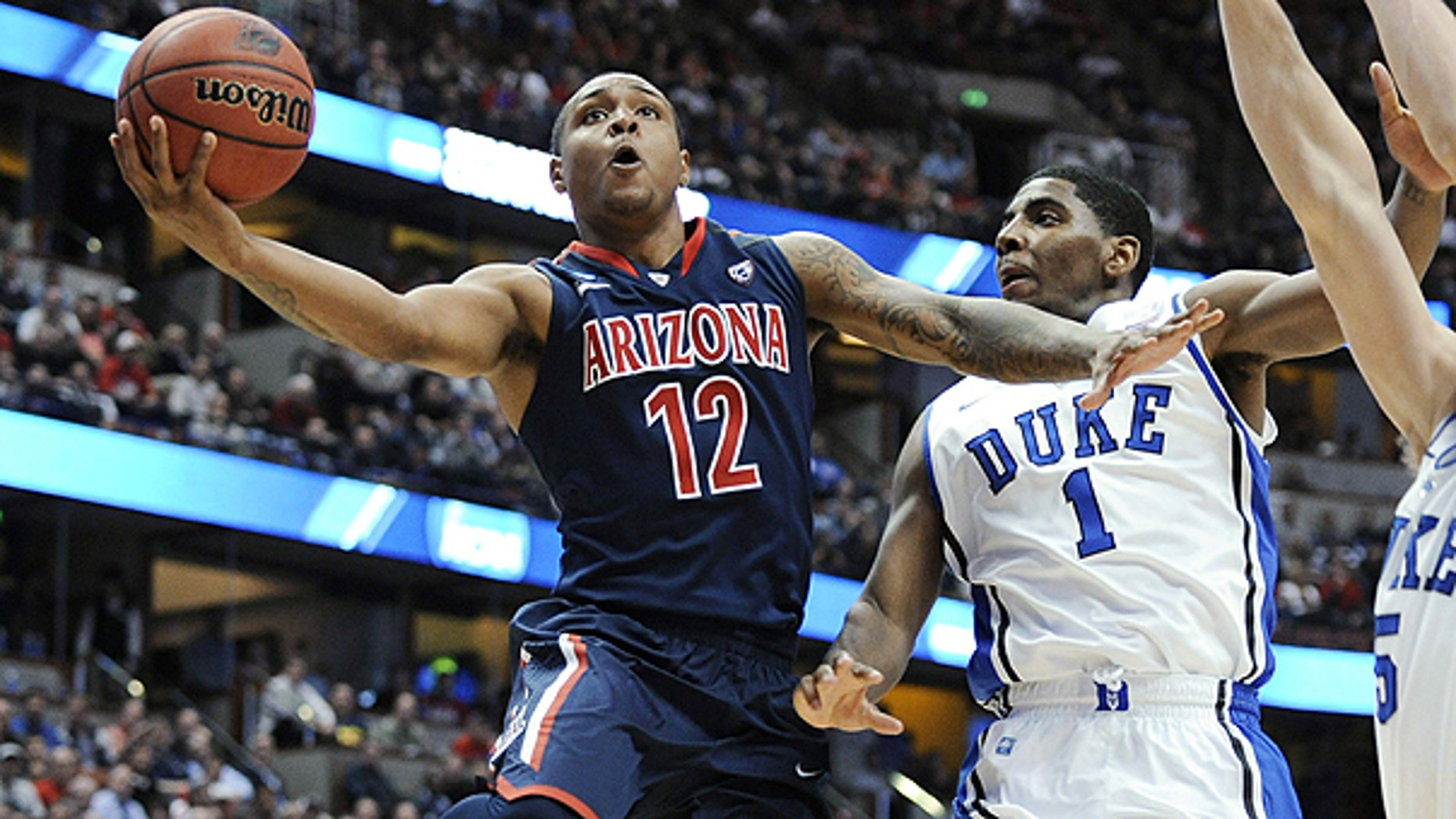 March 24: Arizona's Lamont Jones (12) drives past Duke's Kyrie Irving (1) during the second half of a West regional semifinal in the NCAA college basketball tournament in Anaheim, California.