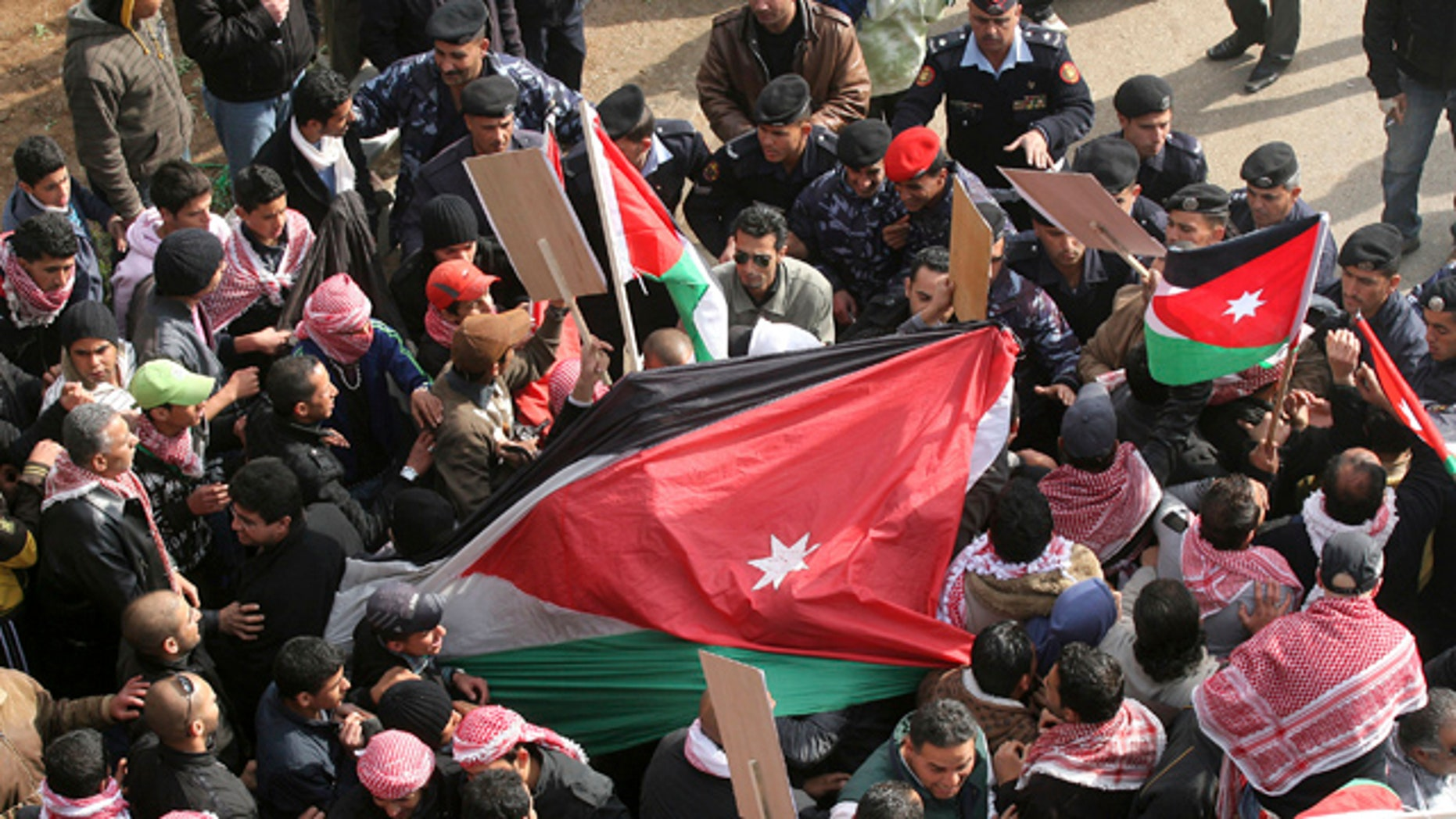 March 25: Jordanian pro-government supporters hold national flags during a rally in Amman, Jordan.