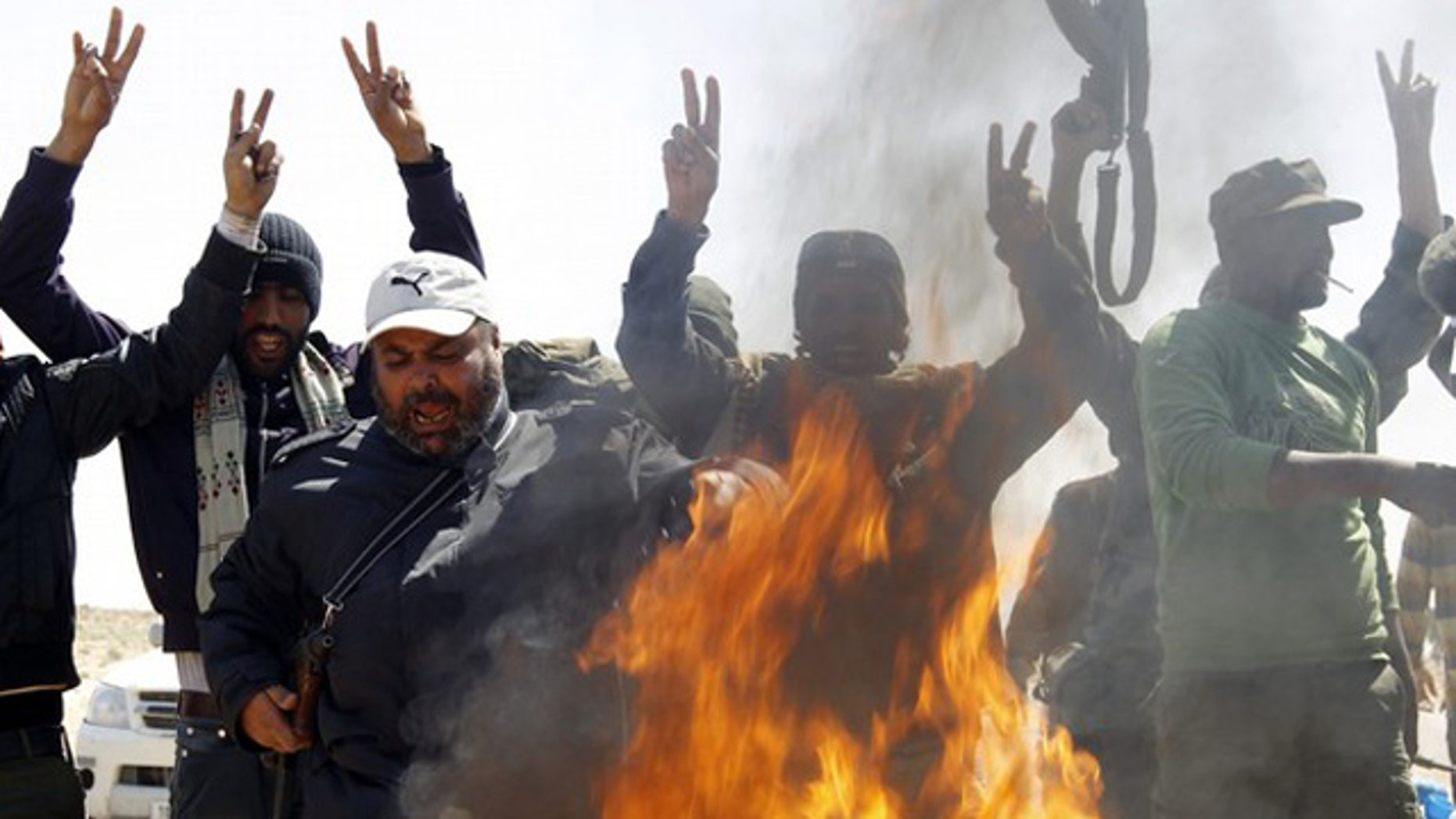 March 25: Rebel fighters shout over a fire ignited to burn clothes of soldiers loyal to Libyan leader Muammar al-Qaddafi along a Benghazi-Ajdabiyah road near Ajdabiyah.