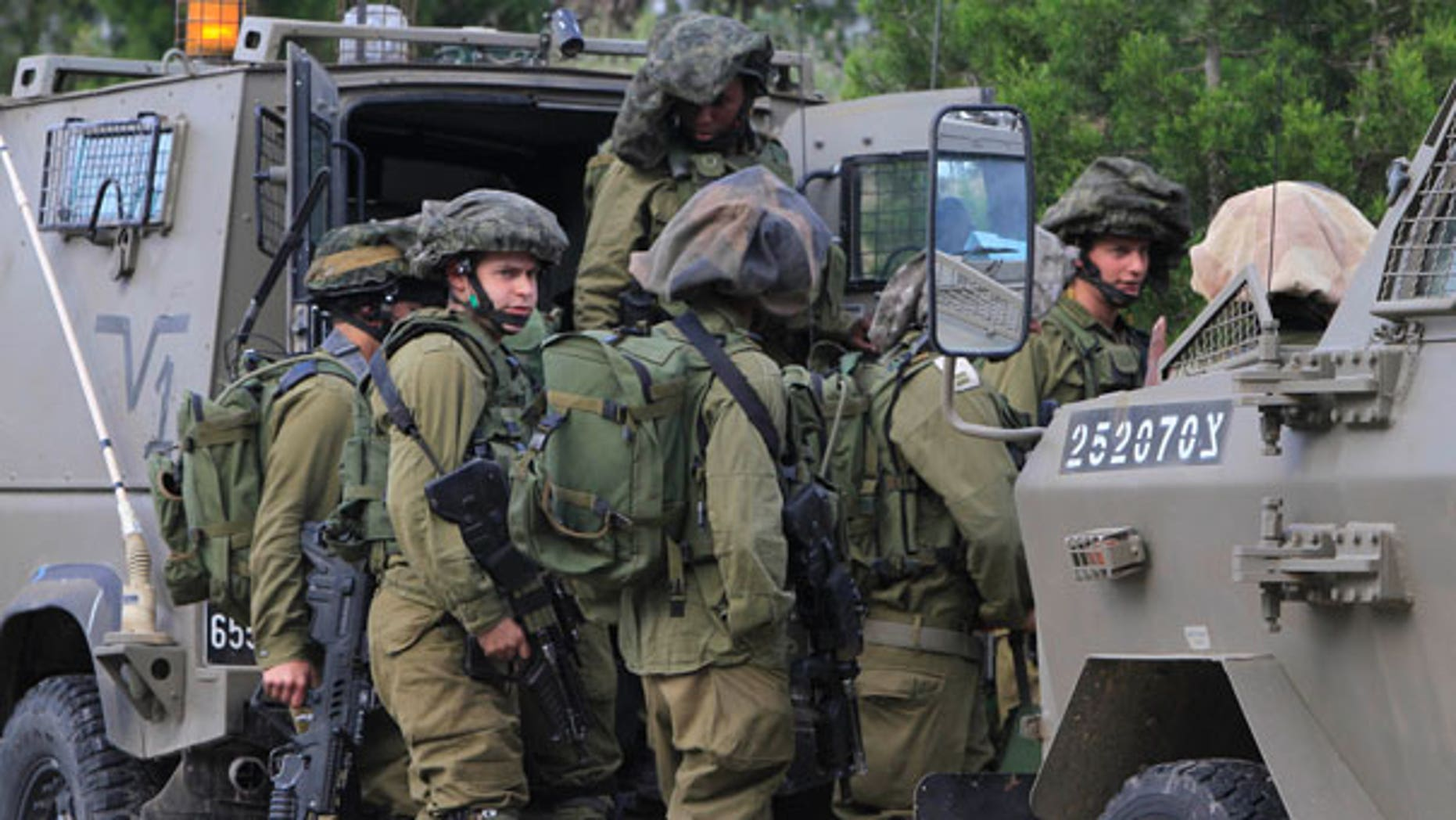 March 26: Israeli soldiers are seen at the Gaza Strip on the border with Israel. The Israeli military says two soldiers have been killed in an exchange of fire with militants who were planting explosives along the security fence in the southern Gaza Strip.
