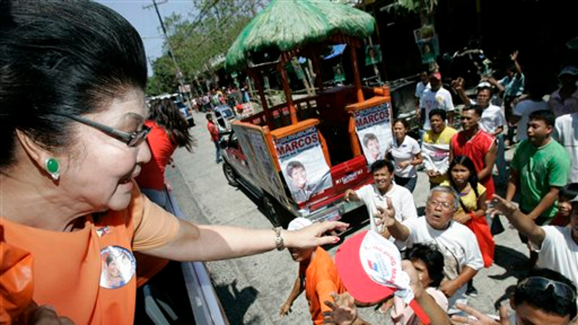 """March 26: Imelda Marcos, left, widow of the late strongman Ferdinand Marcos, gives away caps during a campaign sortie in Batac, Ilocos Norte, northern Philippines. Marcos is running for a seat in the house of representatives along with her son, senatorial bet Ferdinand """"Bongbong"""" Marcos Jr., and her daughter, Imee, a gubernatorial candidate in the Marcos's political stronghold."""