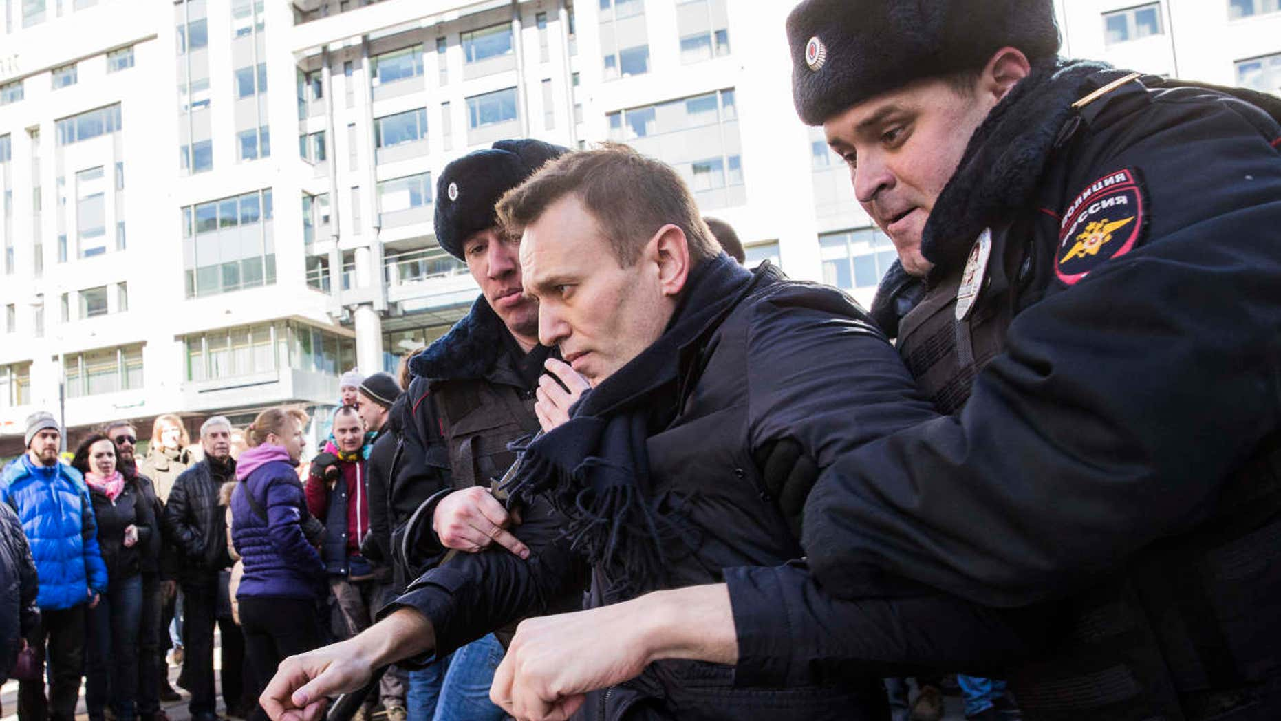 In this photo provided by Evgeny Feldman, Alexei Navalny is detained by police in downtown Moscow, Russia, Sunday, March 26, 2017.