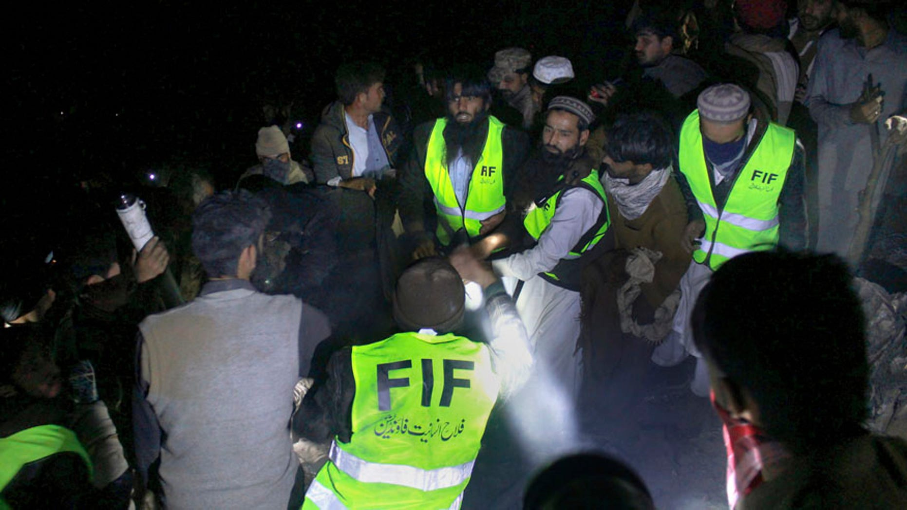 Pakistan army troops and rescue workers collect remains of victims at the site of a plane crash, in a village near the town of Havelian, about 75 kilometers (45 miles) northwest of the capital, Islamabad, Pakistan, Wednesday, Dec. 7, 2016.