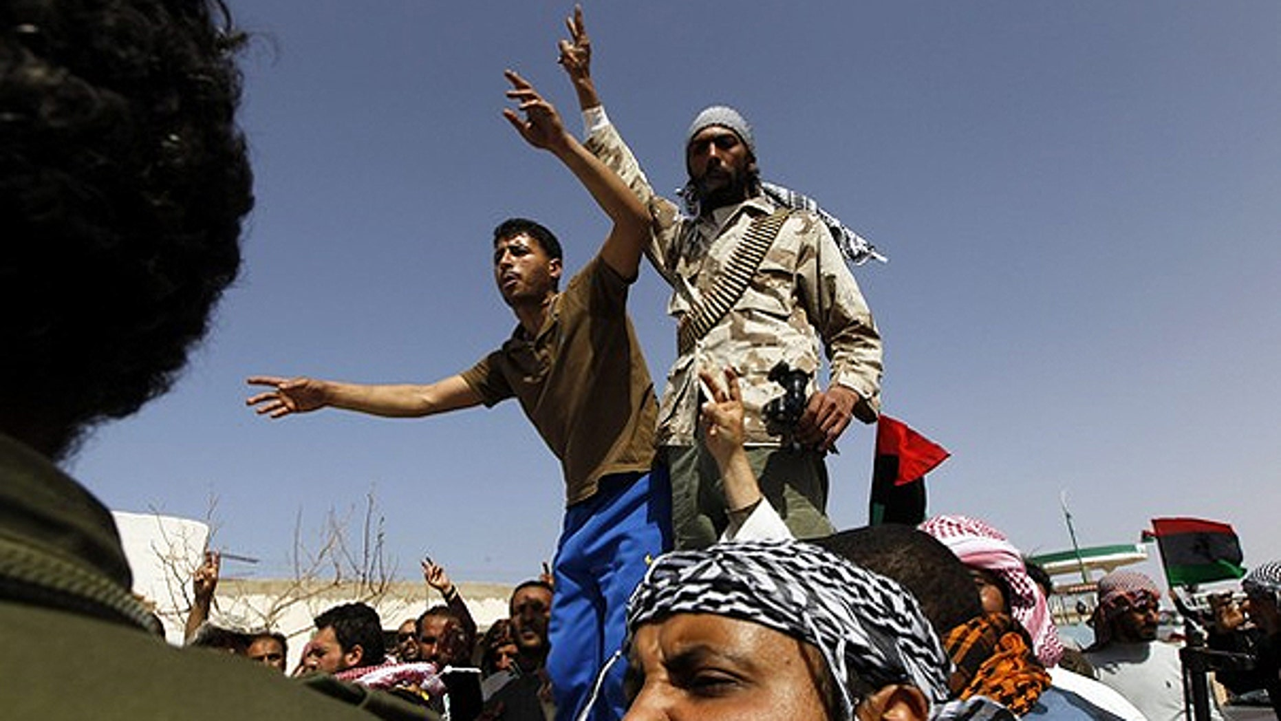 March 28: Libyan rebels react after they found a dead body in the town of Harwa.