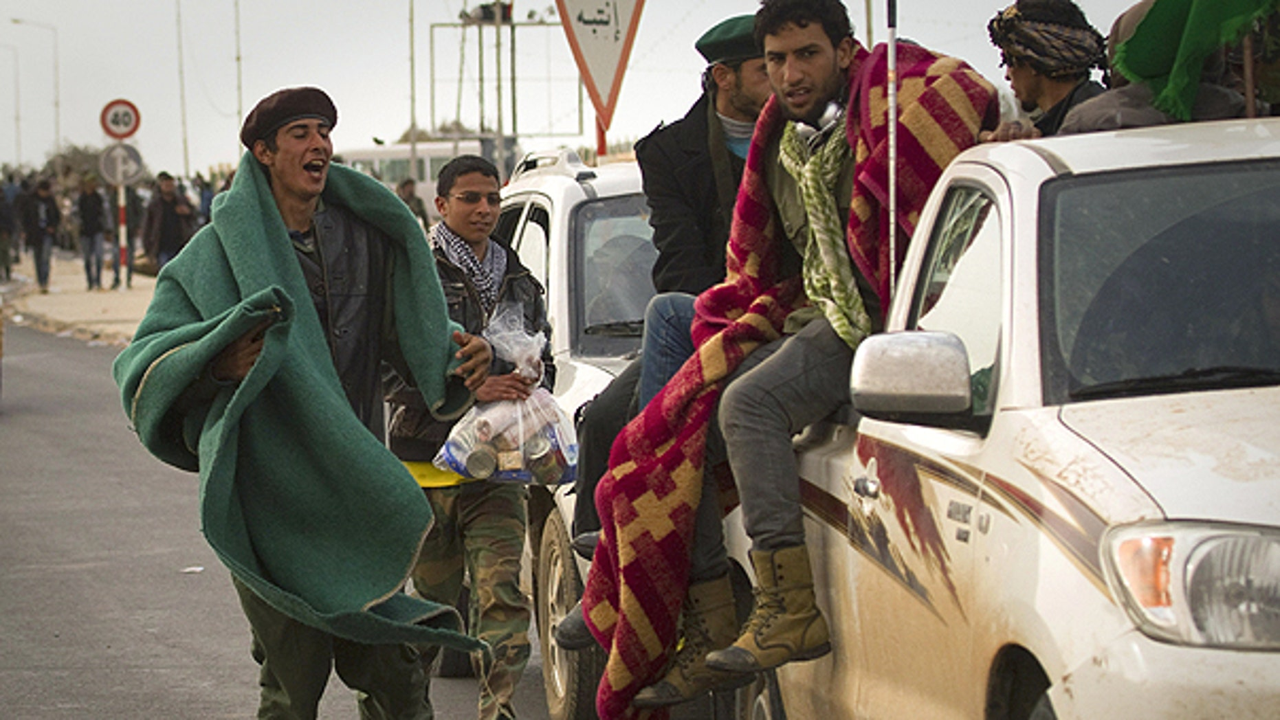 March 29: Libyan rebels run with their belongings as they leave Ras Lanouf, 250 km east of Sirte, central Libya.