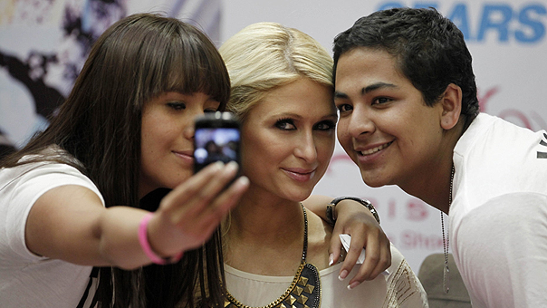 March 29: Paris Hilton poses for a photo with fans during her autograph signing session at a Sears in the Perisur Mall of Mexico City, Mexico.