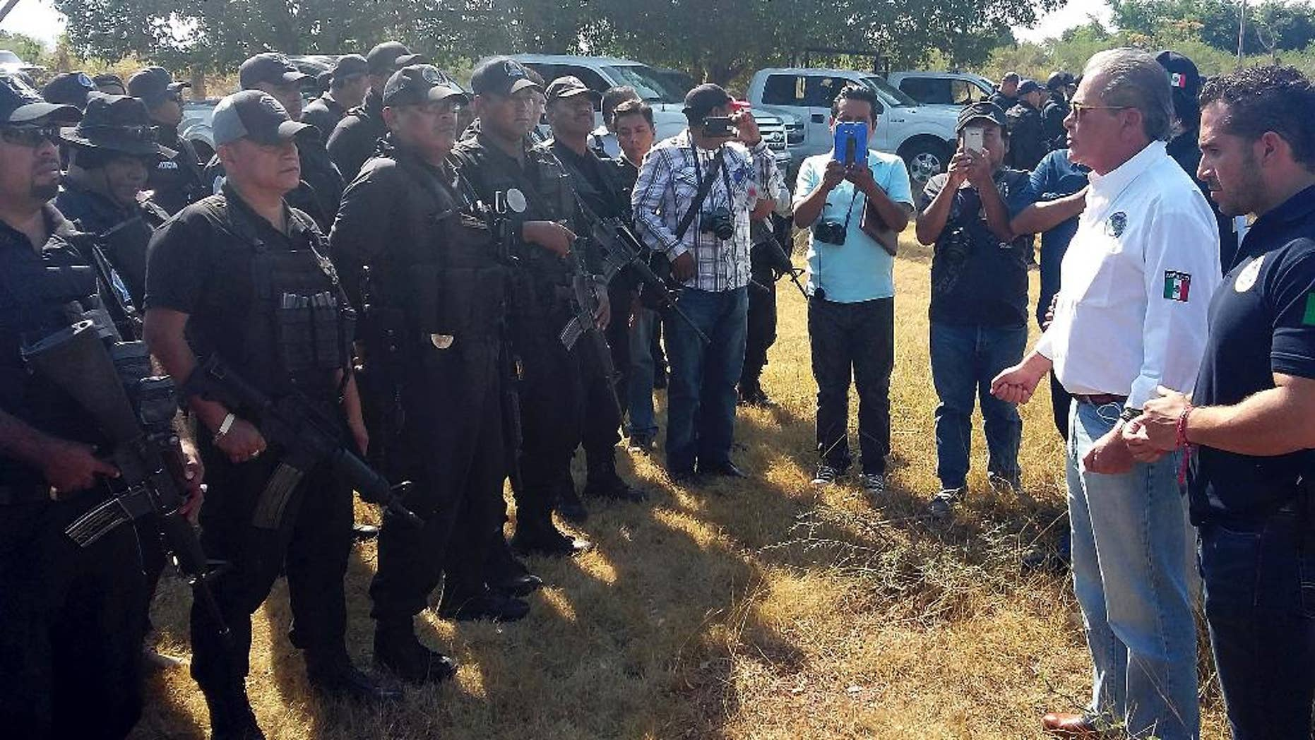 In this photo released by Guerrero state Attorney Generals Office, Javier Olea, attorney general of Guerrero state, right, talks to police at the start of a security operation in San Jeronimo El Grande, Mexico, Thursday, Nov. 24, 2016.  Soldiers and police fanned out Friday across Guerrero state, chasing a wounded gang leader and trying to quell a wave of violence that included the discovery of hidden graves holding dozens of bodies and a camp where gunmen stored the severed heads of nine rivals in a cooler. (Guerrero state Attorney Generals Office via AP)