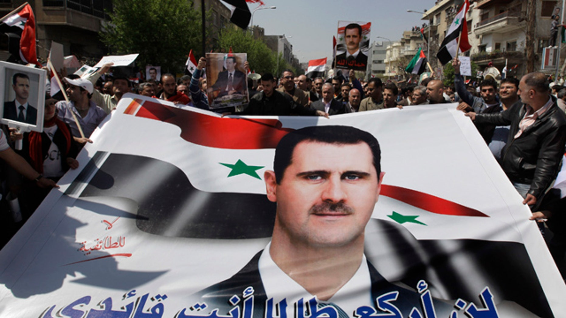 "March 29: Pro-Syrian President Bashar Assad supporters hold Assad's poster with Arabic words reading: ""I'll not kneel as long as you are my leader"" as they demonstrate to show their support for their president, in Damascus, Syria."