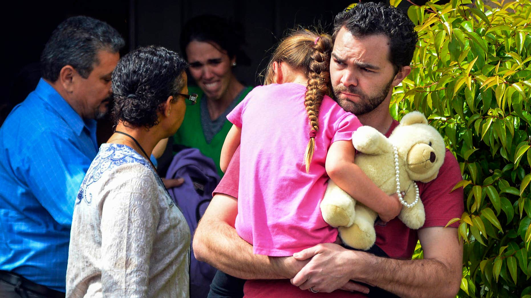 FILE - In this March 21, 2016 file photo, Rusty Page carries Lexi while Summer Page, in the background, cries as members of family services, left, arrive to take Lexi away from her foster family in Santa Clarita, Calif.
