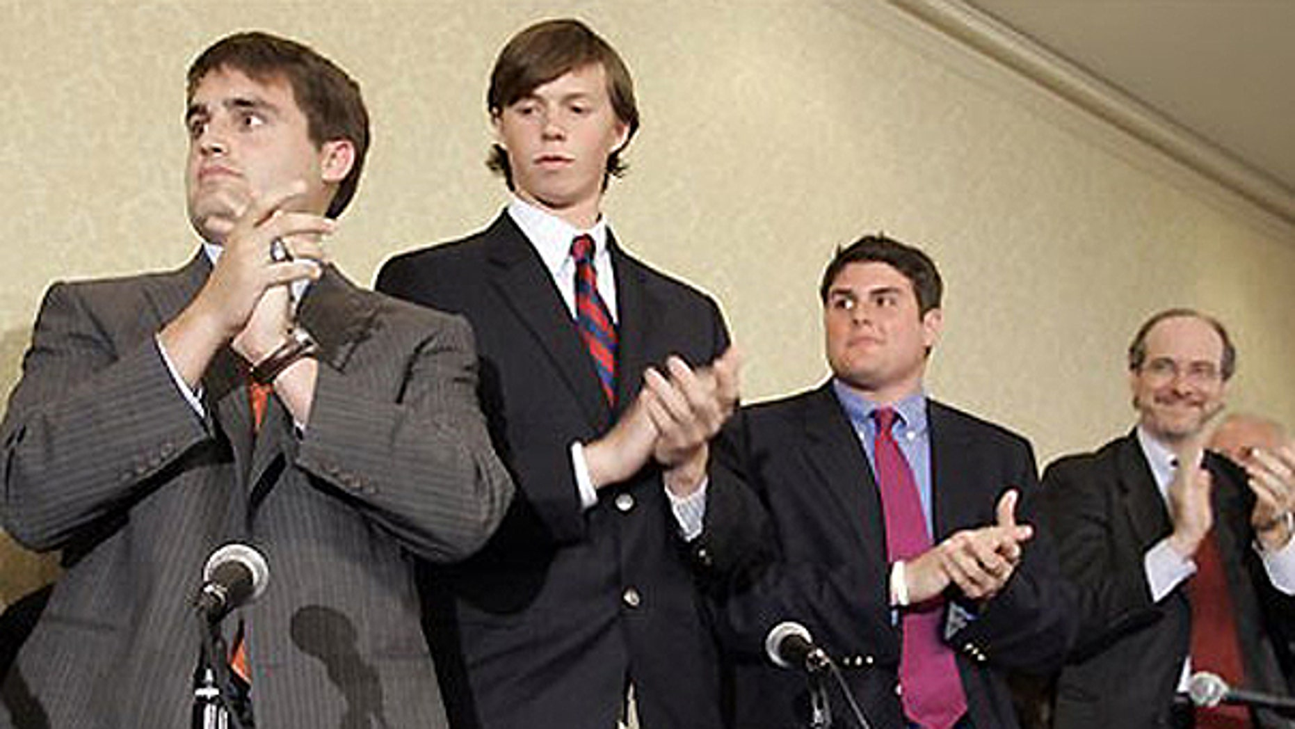 In this April 11, 2006, file photo, from left, David Evans, Collin Finnerty, Reade Seligmann, and lawyer Jim Cooney, right, applaud during a news conference in Raleigh, N.C.