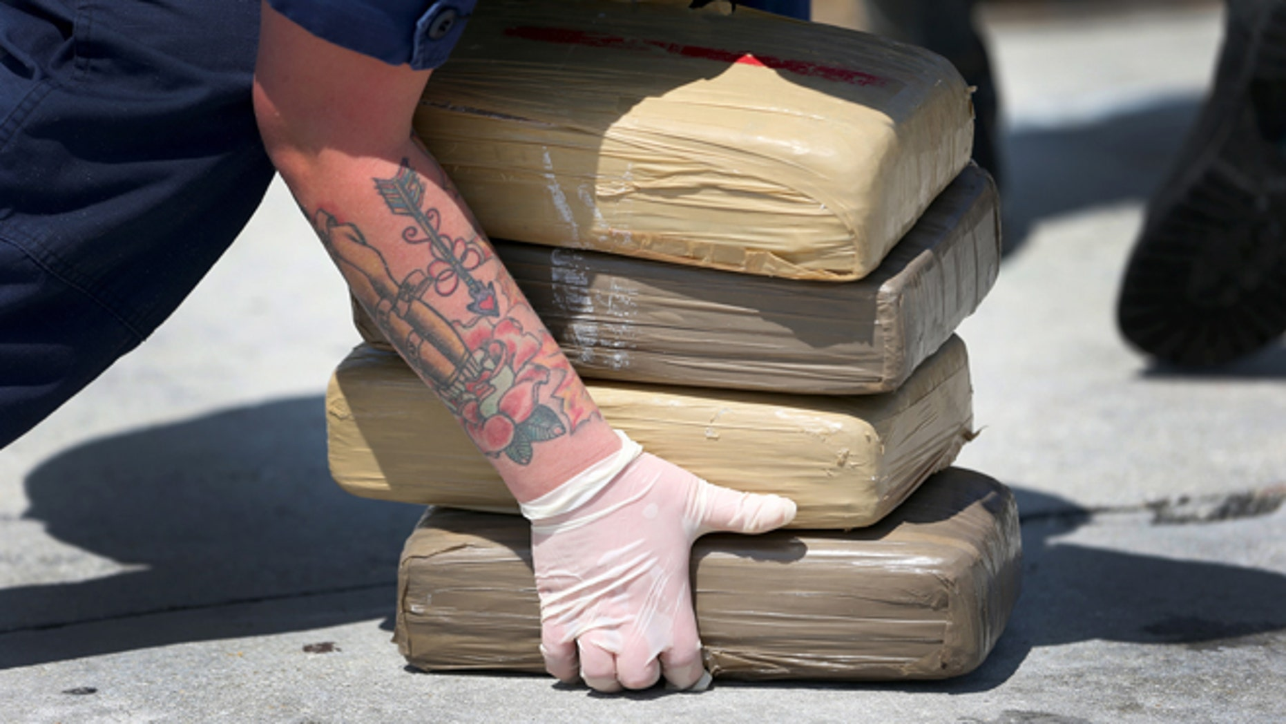 MIAMI BEACH, FL - MAY 09:  A U.S. Coast Guard crew member off loads blocks of marijuana from the Paul Clark one of the Coast Guard's newest fast-response cutters on May 9, 2014 in Miami Beach, Florida.  The U.S. Coast Guard used two of the new fast-response cutters to seize the more than $3 million in drugs earlier this month on the Caribbean Sea in separate interdictions just a day apart from each other.  (Photo by Joe Raedle/Getty Images)
