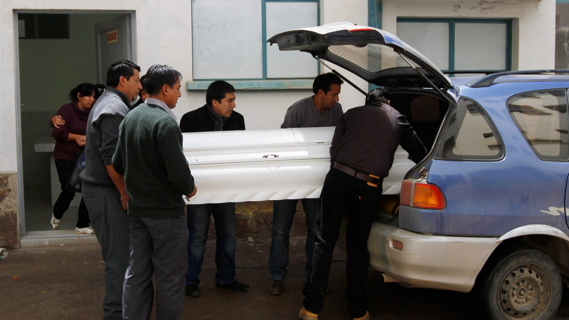 Relatives place the coffin containing the remains of Kevin Beltran Estrada, who died after an explosive went off during a soccer game, into a car in Oruro, Bolivia, Thursday, Feb. 21, 2013.  Twelve Corinthian soccer fans were arrested on suspicion of having caused the death of a 14-year-old San Jose soccer fan by launching an explosive device during a Copa Libertadores game between San Jose and Corinthians on Wednesday in the Bolivian city of Oruro, according to police. (AP Photo/Juan Karita)