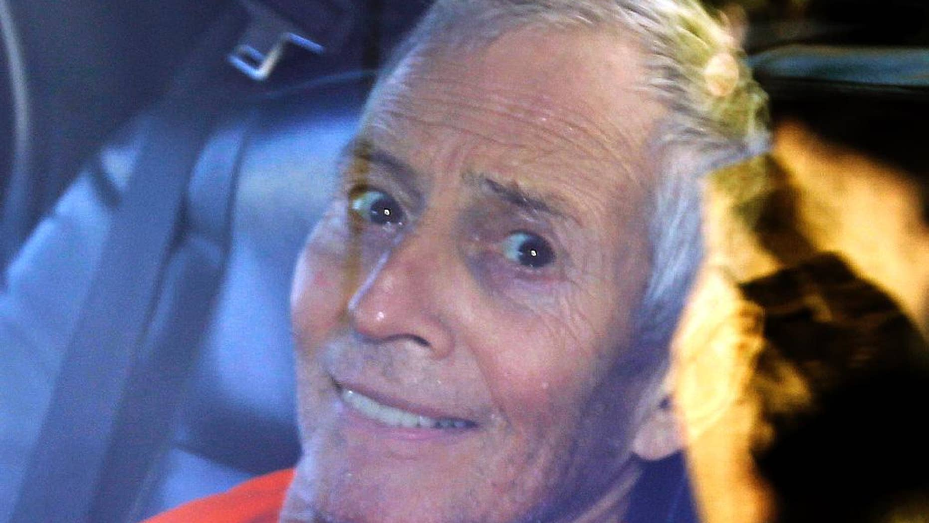 FILE - In this Tuesday, March 17, 2015, file photo, millionaire Robert Durst is escorted from Orleans Parish Criminal District Court to the Orleans Parish Prison after his arraignment in New Orleans. Durst returns to court Thursday, April 2, 2015, where his attorneys plan to argue that the FBI searched his room illegally and police covered this up in statements used to get an arrest warrant on Louisiana weapons charges. (AP Photo/Gerald Herbert, File)