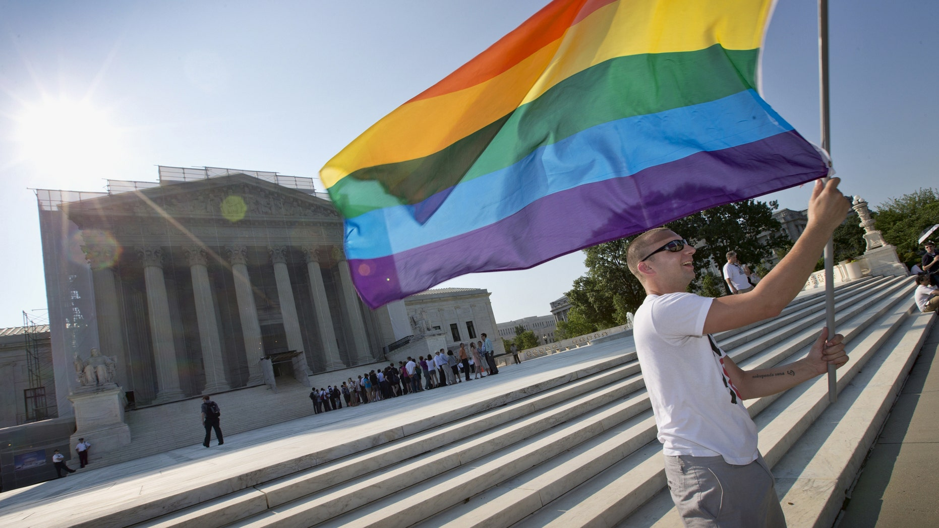 FILE - In this June 25, 2013 file photo, Vin Testa of Washington waves a rainbow flag in support of gay rights outside the Supreme Court in Washington.  The Supreme Court will hear arguments over same-sex marriage on April 28 and make audio of the proceedings available later that day. The gay marriage cases mark the only time this term that the court has agreed to the quick release of audio recordings. But the court is continuing its ban on providing video of its sessions or even live-streamed audio. (AP Photo/J. Scott Applewhite, File)