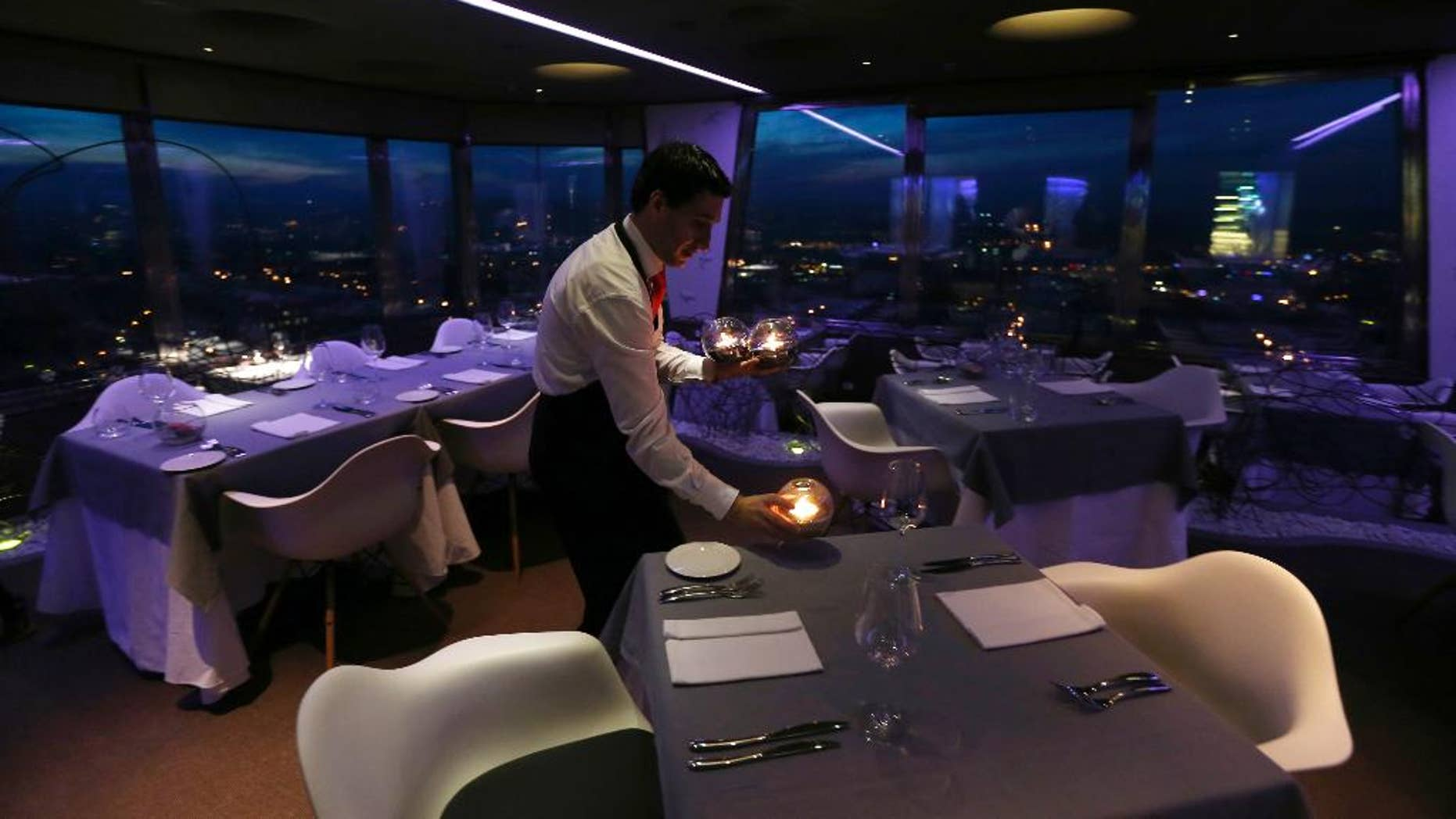 FILE- In this March 6, 2013 file photo, a waiter sets a candle on a table in a restaurant at the Zizkov television tower in Prague, Czech Republic. The Czech Republic has launched a new system to increase tax revenue by requiring bars and restaurants to report their sales online.   (AP Photo/Petr David Josek)