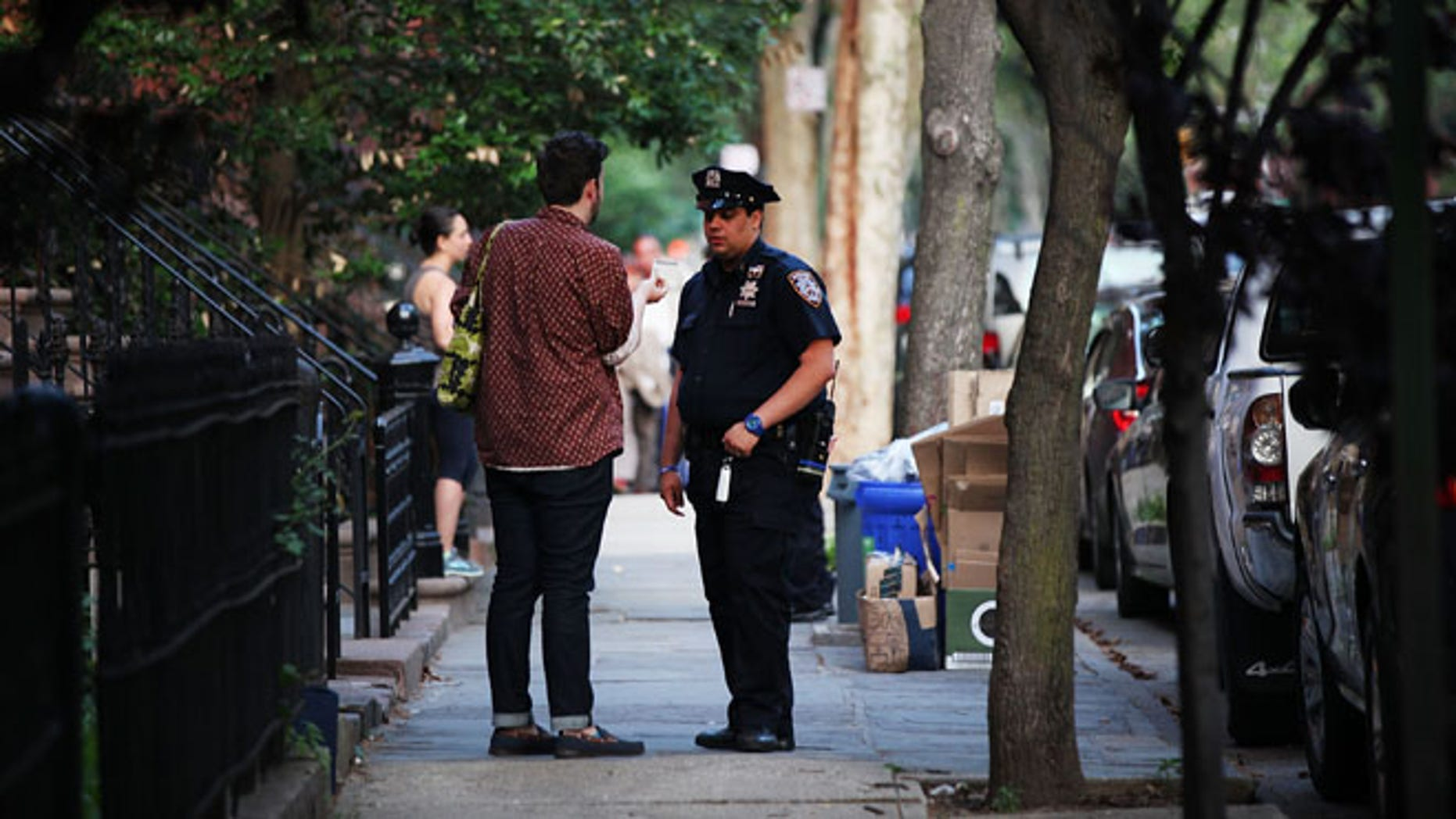 """NEW YORK, NY - JUNE 10:  Police officers are seen by a crime scene where three people were shot on June 10, 2015 in the Gowanus area of the Brooklyn Borough of New York City. In an effort to combat the rise in murders and shootings, hundreds of additional New York City Police Officers will begin walking city streets as part of an aggressive NYPD initiative called """"Summer All Out."""" About 330 officers will be taken off of administrative duty to patrol the streets in some of the city's most violent neighborhoods.  (Photo by Spencer Platt/Getty Images)"""