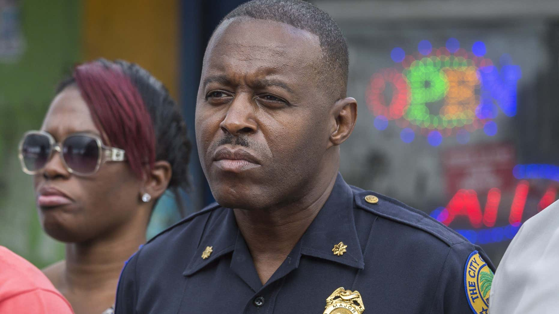 """In this Jan. 2, 2016, photo, Miami Police Maj. Delrish Moss stands among the Miami-Dade officials who announced the arrest of Willie """"Pee Wee"""" Wilcher in Liberty City, Fla."""