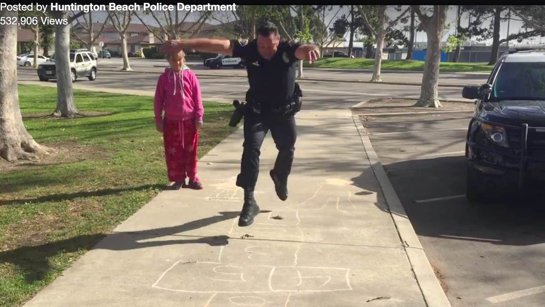 In this Wednesday, March 30, 2016 still frame from video provided by the Huntington Beach, Calif., Police Department, Officer Zach Pricer shows an 11-year-old homeless girl how to hopscotch on a street in Huntington Beach, Calif.