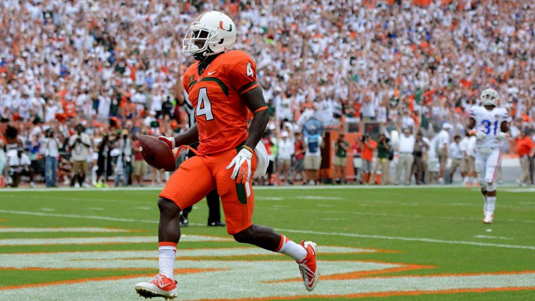 Sep 7, 2013; Miami Gardens, FL, USA; Miami Hurricanes wide receiver Phillip Dorsett (4) scores untouched against the Florida Gators during the first half of the game at Sun Life Stadium. Mandatory Credit: Brad Barr-USA TODAY Sports