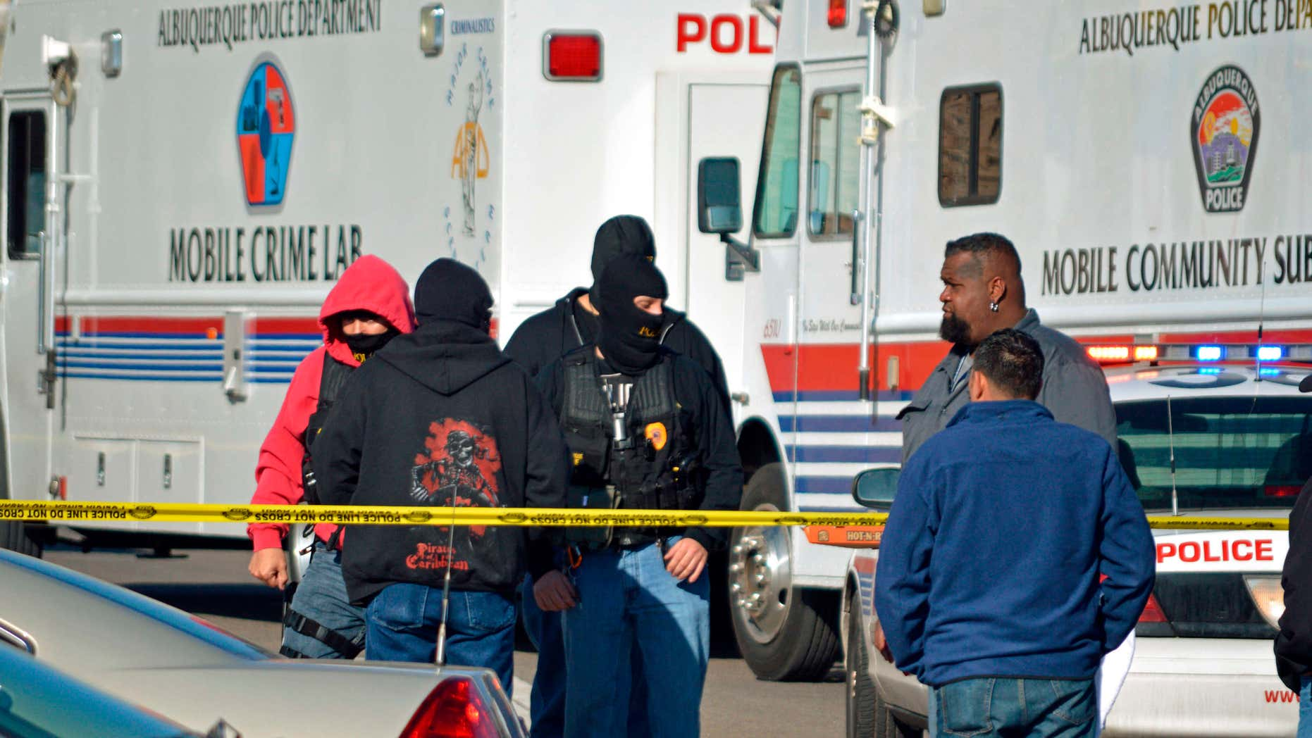 FILE - This Jan. 9, 2015 file photo, Investigators search a busy intersection in Albuquerque, N.M., after police say an undercover detective shot another undercover detective during a drug sting.