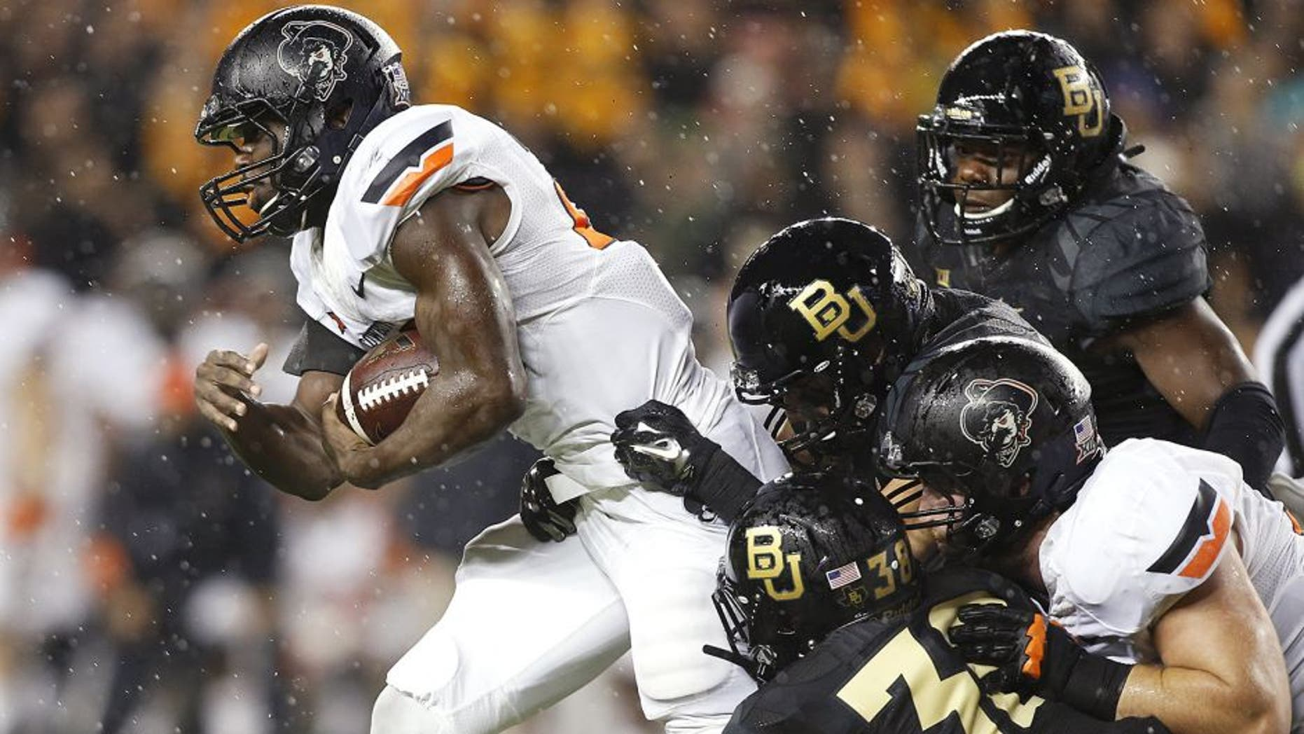 Nov 22, 2014; Waco, TX, USA; Oklahoma State Cowboys running back Rennie Childs (23) is gang tackled with the gal in the third quarter at McLane Stadium. Baylor beat Oklahoma State 49-28. Mandatory Credit: Tim Heitman-USA TODAY Sports