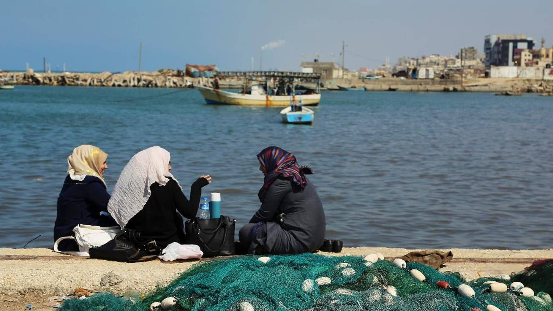 Palestinian women chat while enjoying the sunny weather at the fishermen's port in Gaza City in the northern Gaza Strip on Thursday, March 5, 2015. (AP Photo/Adel Hana)