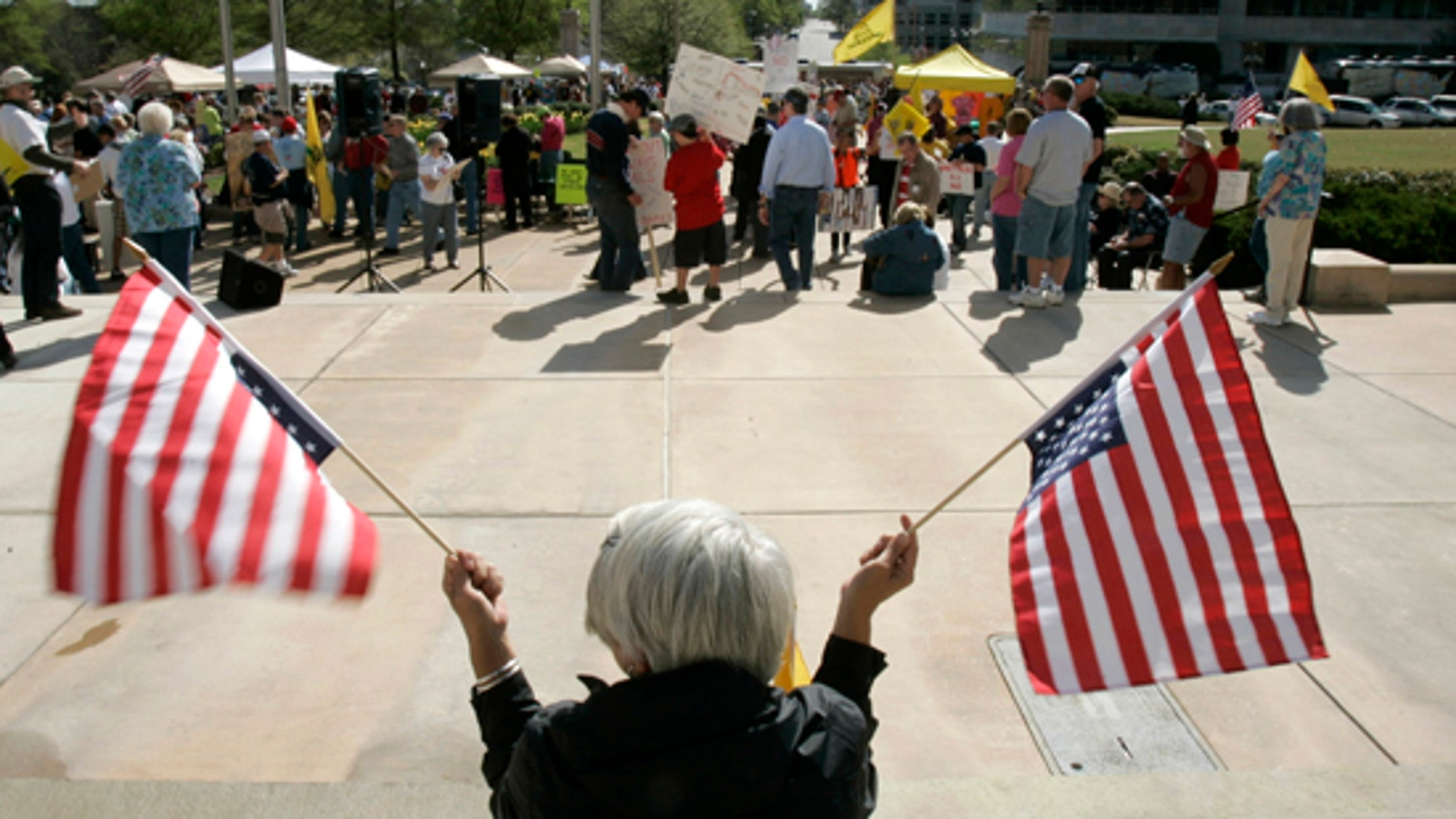 An unidentified woman holds upside-down flags before a Tea Party Express rally at the Arkansas state Capitol in Little Rock, Ark., Saturday, April 3, 2010.(AP)