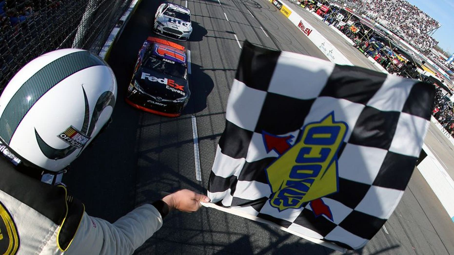 MARTINSVILLE, VA - MARCH 29: Denny Hamlin, driver of the #11 FedEx Express Toyota, takes the checkered flag to win the NASCAR Sprint Cup Series STP 500 at Martinsville Speedway on March 29, 2015 in Martinsville, Virginia. (Photo by Nick Laham/NASCAR via Getty Images)